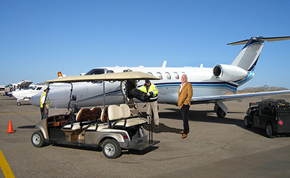 CST Flight Services agent helping unload Citation CJ3 with owner and golf cart waiting