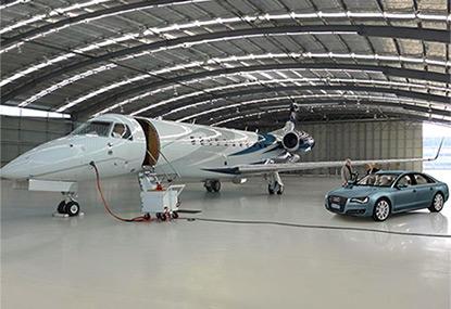 Embraer in hangar with customers arriving in luxury car